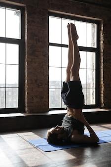 Skoncentrowany silny sportowiec na siłowni wykonuje ćwiczenia jogi.