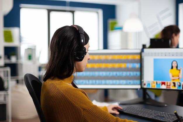 Skoncentrowany specjalista od retuszu, pracujący przy komputerze w kreatywnym środowisku biurowym, noszący zestaw słuchawkowy