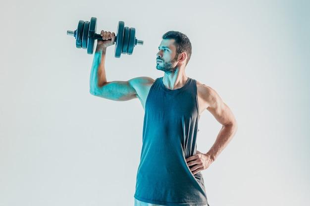 Skoncentrowany sportowiec trenujący mięśnie ramion z hantlami. młody brodaty mężczyzna europejski nosić mundur sportowy. na białym tle na turkusowym tle. sesja studyjna. skopiuj miejsce