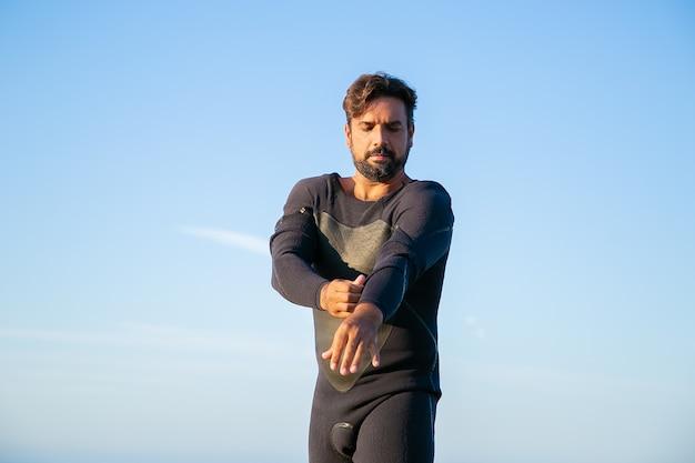 Skoncentrowany sportowiec zakładający piankę do surfowania na plaży oceanu