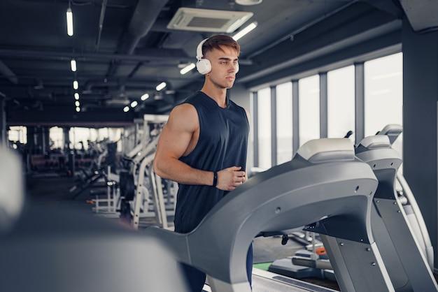 Skoncentrowany, sprawny mężczyzna słuchający muzyki w słuchawkach podczas biegania na bieżni w nowoczesnej siłowni z panoramicznymi oknami, portret
