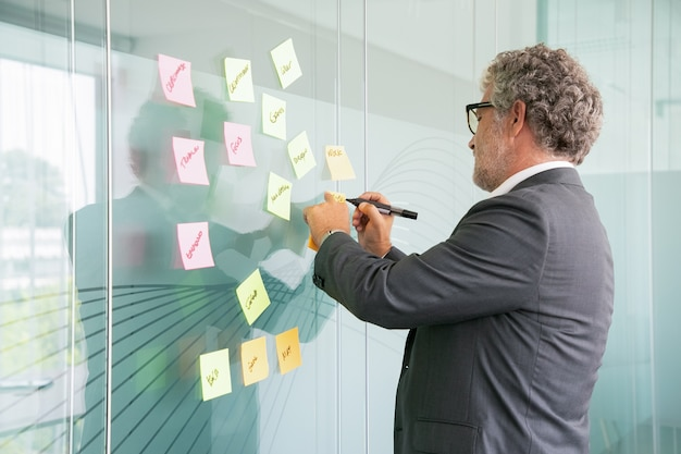 Skoncentrowany starszy biznesmen piszący na naklejce z czarnym markerem