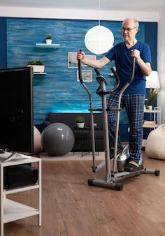 Skoncentrowany starszy mężczyzna na emeryturze pracujący na oporach nóg przy użyciu rowerowej maszyny rowerowej