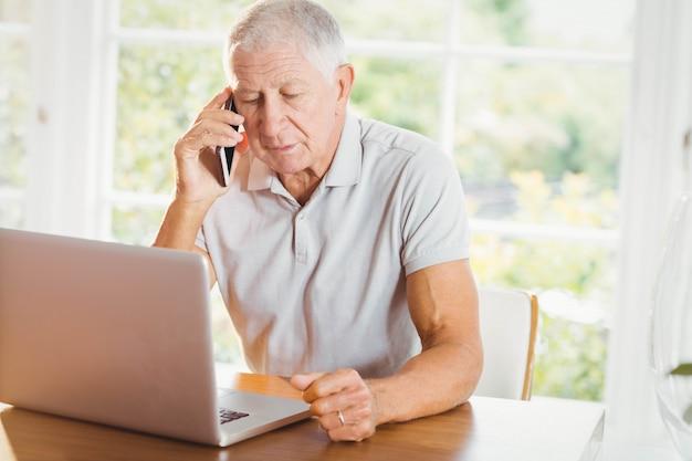 Skoncentrowany starszy mężczyzna patrzeje laptop i telefon dzwoni w domu