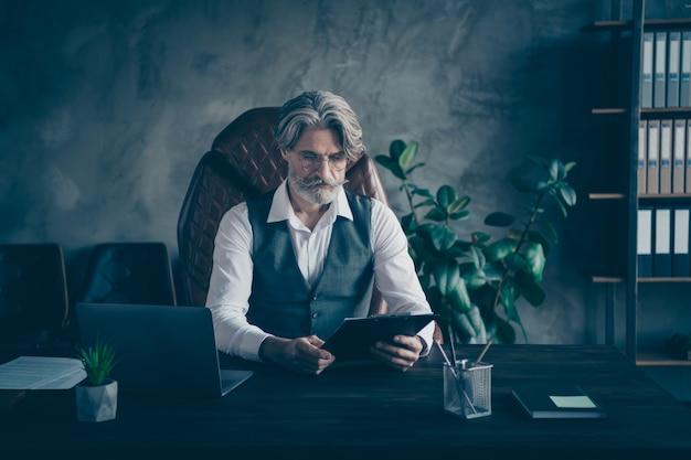 Skoncentrowany stary biznesmen trzymać schowek w nowoczesnym biurze