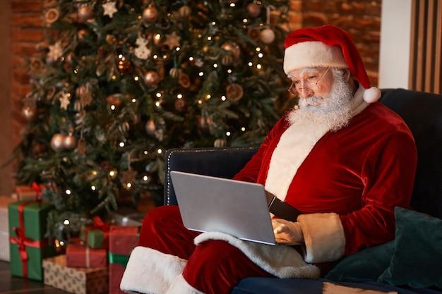 Skoncentrowany stary mikołaj siedzący na kanapie w pobliżu choinki i pracujący z laptopem