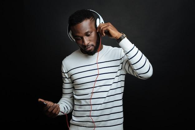 Skoncentrowany sympatyczny mężczyzna korzystający ze smartfona i cieszący się piosenkami, używając słuchawek i stojąc przy czarnej ścianie