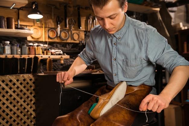 Skoncentrowany szewc w warsztacie produkującym buty