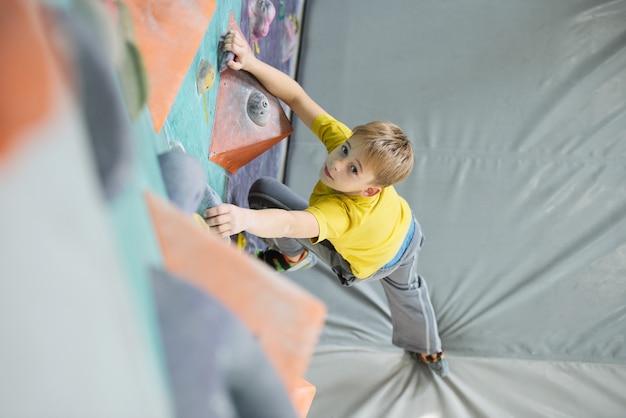 Skoncentrowany uczeń patrzy na ciebie, stojąc na szarej macie i trzymając nogę na skale sprzętu wspinaczkowego podczas treningu