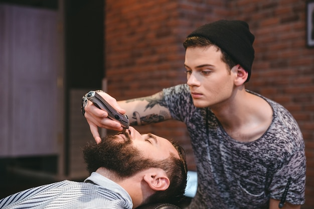 Skoncentrowany umiejętny młody fryzjer przycinający brodę przystojnego młodego mężczyzny w salonie fryzjerskim