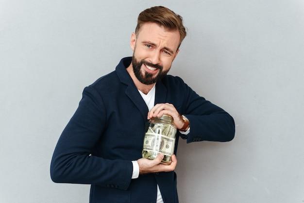 Skoncentrowany uśmiechnięty brodaty mężczyzna próbuje otwierać słój w biznesów ubraniach