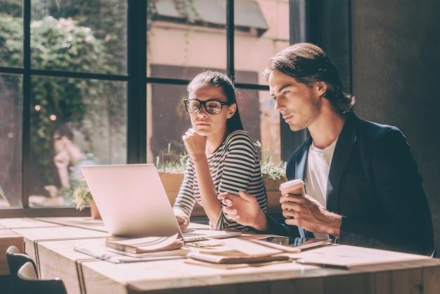 Skoncentrowany w pracy. pewny siebie młody mężczyzna i kobieta patrzący na laptopa siedząc przy drewnianym biurku w kreatywnym biurze lub kawiarni