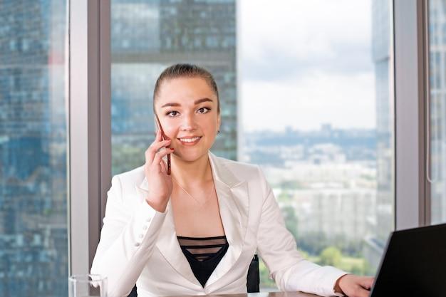 Skoncentrowany w pracy. przekonana, młoda kobieta w elegancki casual pracy na laptopie, siedząc w pobliżu okna w kreatywnym biurze.