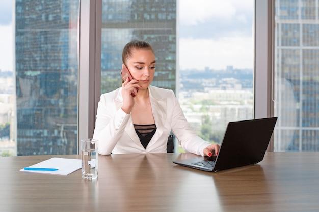 Skoncentrowany w pracy. ufna młoda kobieta w mądrze przypadkowej odzieży pracuje na laptopie podczas gdy siedzący blisko okno w kreatywnie biurze