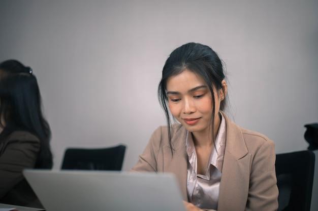 Skoncentrowany wieloetniczny współpracownik zajęty burzą mózgów na laptopie, dzieląc się przemyśleniami na spotkaniu w biurze