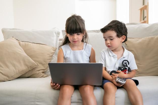 Skoncentrowany zamyślony braciszek i siostra siedzą na kanapie w domu, używają laptopa do rozmowy wideo lub oglądają wideo lub film.