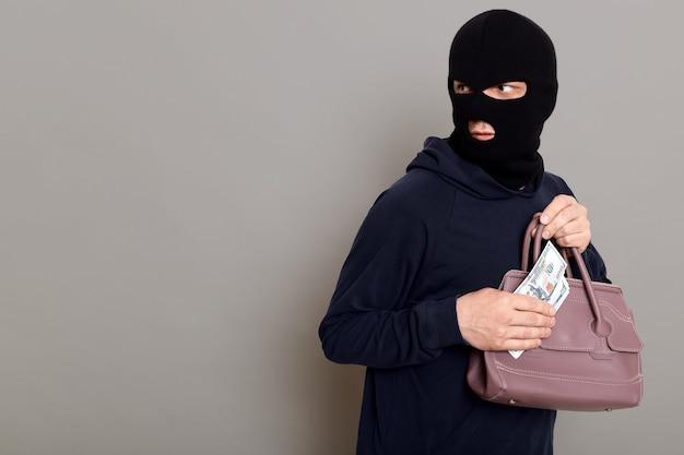 Skoncentrowany złodziej sukienki w kominiarce i czarnym golfie spogląda wstecz i trzyma w rękach pieniądze oraz skradzioną torebkę kobiety