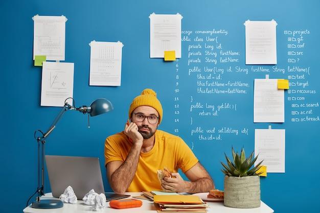 Skoncentrowany zmęczony uczeń w żółtym ubraniu przygotowuje projekt pracy domowej
