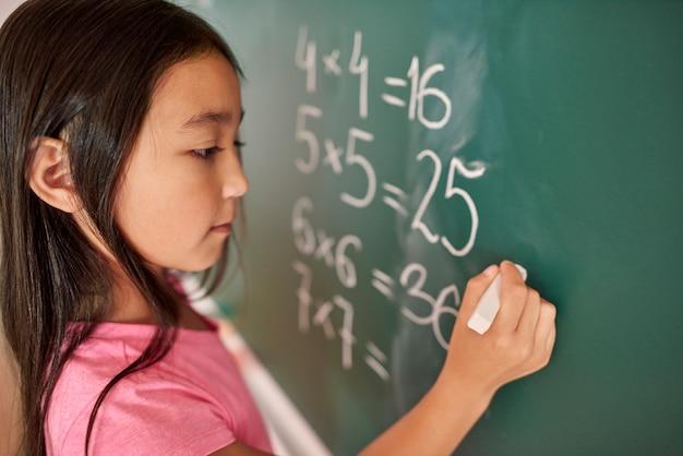 Skoncentruj się dziewczyna próbuje rozwiązać równanie matematyczne