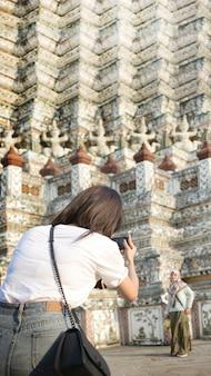Skoncentruj się kobieta ręcznie przechwytuj zdjęcie za pomocą telefonu komórkowego na temat turystyki architektury w publicznej świątyni w bangkoku w tajlandii - rozmiar pionowego transparentu