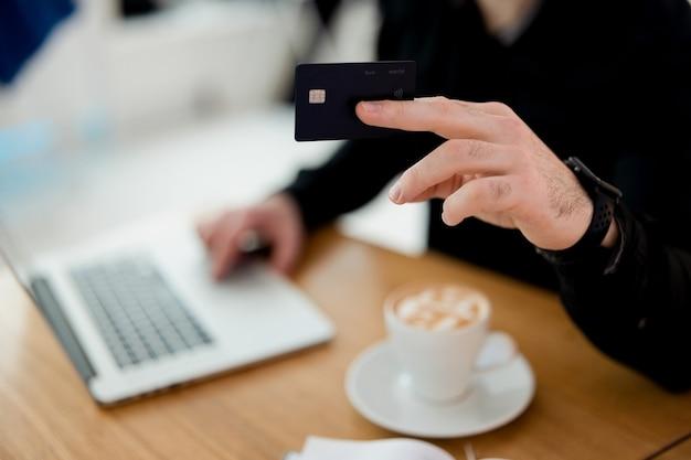 Skoncentruj się na czarnej karcie kredytowej. mężczyzna jest gotów zapłacić za swoje zamówienie w kawiarni. trzyma kartę do baristy. niewyraźne męskie ciało w czarnej koszuli, laptopie i filiżance kawy na stole. widok cięcia.