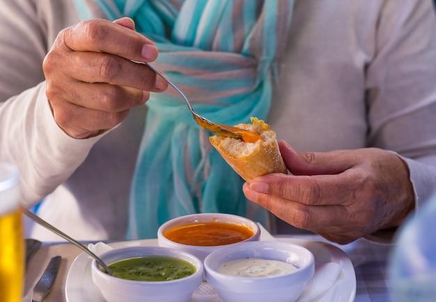"""Skoncentruj się na dłoniach kobiety delektującej się trzema typowymi dla wysp kanaryjskich sosami, zwanymi """"mojo"""""""