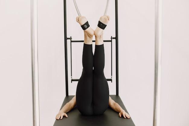 Skoncentruj się na kobiecych nogach i tyłku. kobieta ubrana w czarną odzież sportową. dziewczyna kaukaski rozciąganie ze sprzętem.