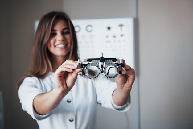 Skoncentruj się na okularach. kobieta lekarz stojący w biurze i trzymając specjalne okulary z tablicą do badania ostrości wzroku