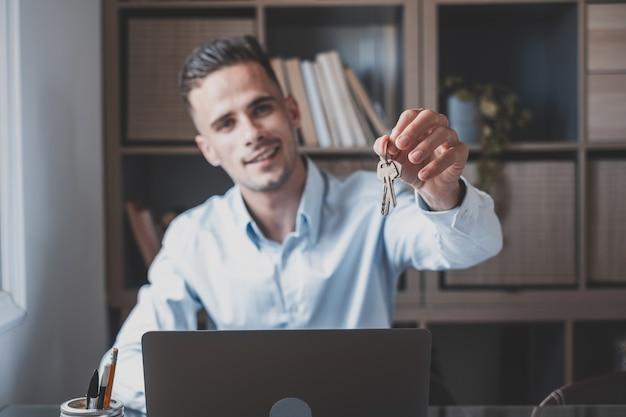 Skoncentruj się na pęku kluczy z mieszkania w domu w ręku uśmiechniętego mężczyzny. niewyraźne portret pewny siebie mężczyzna profesjonalny pośrednik w handlu nieruchomościami oferujący nowe mieszkanie dla potencjalnego nabywcy. ścieśniać