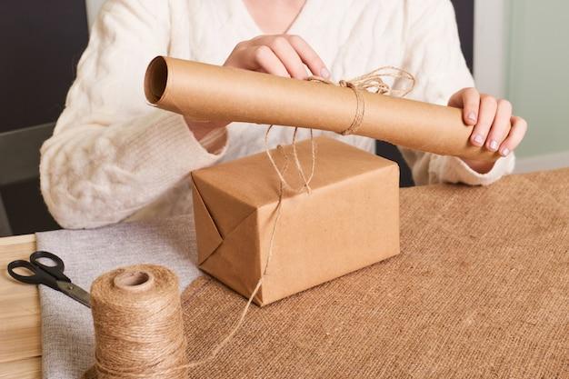 Skoncentruj się na rękach kobiety w białym pudełku z dzianiny. papier do pakowania rzemieślniczego i naturalny sznurek. szczęśliwy prezent świąteczny, niespodzianka. prezenty na drugi dzień świąt