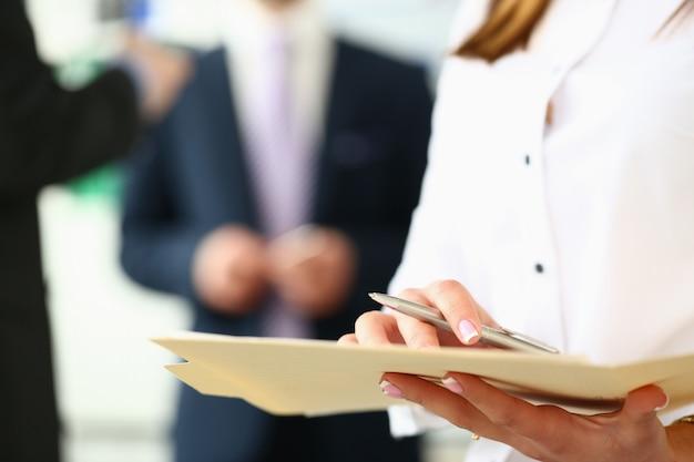 Skoncentruj się na sekretarce z ładnym manicure sprawdzającym ważny kontrakt biznesowy z koncentracją w nowoczesnym biurze.