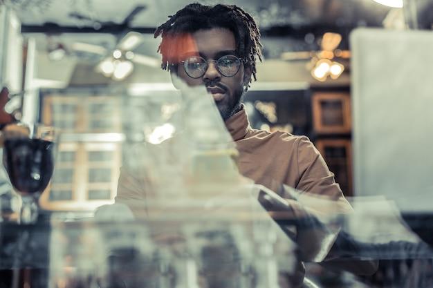 Skoncentruj się na zadaniu. skoncentrowany stylowy mężczyzna trzymający telefon w obu rękach siedząc przy stole