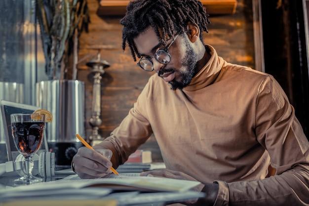 Skoncentruj się na zadaniu. zadowolony młody człowiek pochylający głowę, patrząc na swoje notatki