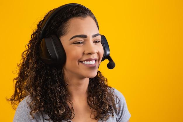 Skontaktuj się z centrum obsługi telefonicznej. obsługa klienta, agentka sprzedaży. rozmówca lub operator operatora telefonicznego lub kobieta biznesu w zestawie słuchawkowym. afro młoda kobieta. powiększ konferencję. żółte tło