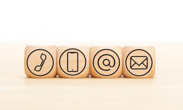 Skontaktuj się z nami ikony w drewnianych klockach na drewnianym biurku. skopiuj miejsce.