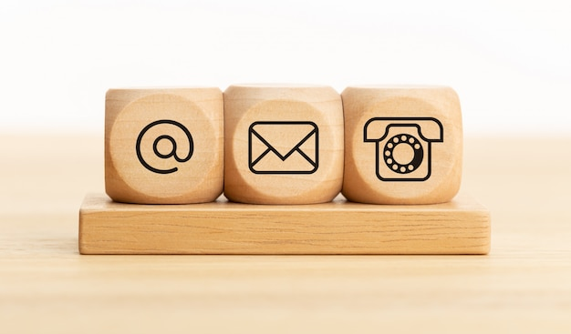 Skontaktuj się z nami koncepcja. drewniane klocki z ikonami email, mail i telefon. strona internetowa kontakt lub marketing e-mailowy