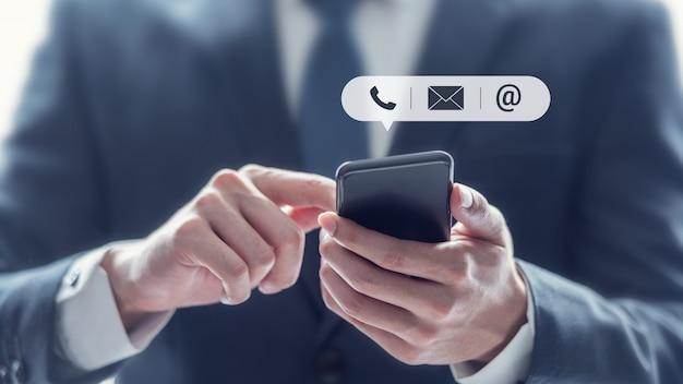 Skontaktuj się z nami, ręka biznesmena trzyma telefon komórkowy z ikoną (poczta, telefon, e-mail).
