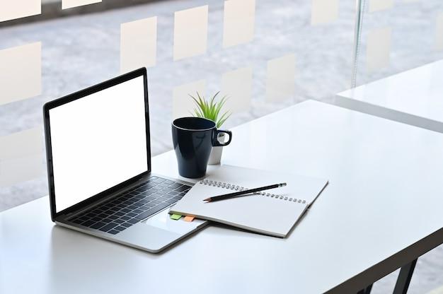 Skopiuj laptop miejsca, makiety pusty ekran i materiały biurowe z kawą na stole.