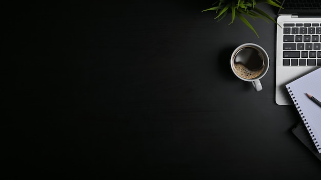 Skopiuj miejsce czarny stół biurowy z laptopem, notatnikiem, ołówkiem i filiżanką kawy z plat.