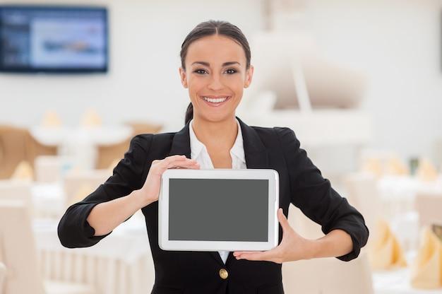 Skopiuj miejsce na jej tablecie. piękna młoda kobieta w stroju formalnym pokazująca swój cyfrowy tablet i uśmiechnięta stojąc w restauracji