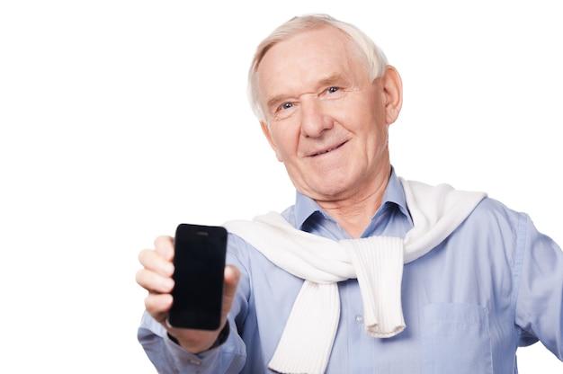 Skopiuj miejsce na moim telefonie. portret szczęśliwego starszego mężczyzny pokazującego swój telefon komórkowy stojąc na białym tle