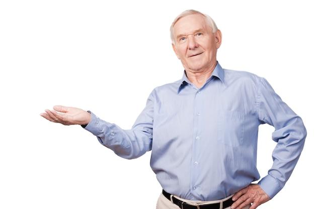 Skopiuj miejsce na mojej dłoni. pewny siebie starszy mężczyzna w koszuli, trzymający miejsce na kopię i patrzący na kamerę, stojąc na białym tle