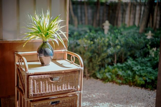 Skopiuj miejsce po prawej stronie, deseń z wazonem i talerzem o silnym słońcu na półce bambusowej.