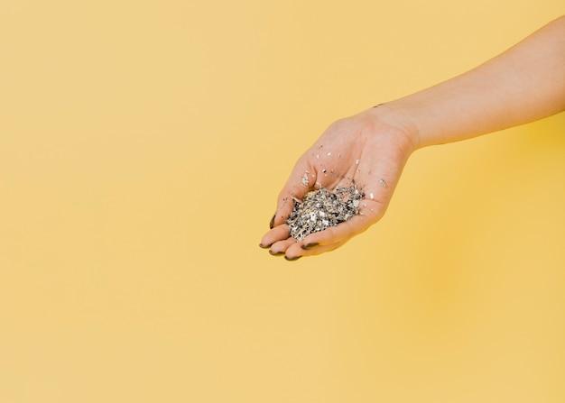 Skopiuj miejsce pomarańczowe tło ręką i brokatem