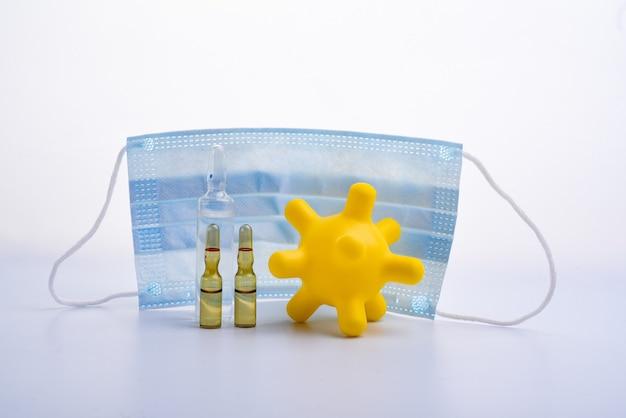 Skopiuj miejsce przezroczyste ampułki medyczne z rzędu. kolorowe zabawki dla dzieci w postaci wirusów. maska medyczna i ampułki chronią przed wirusem. odosobniony