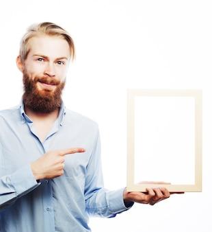 Skopiuj miejsce w ramce obrazu. przystojny młody brodaty mężczyzna w niebieskiej koszuli trzyma ramkę na zdjęcia i wskazuje ją z uśmiechem, stojąc na białym tle