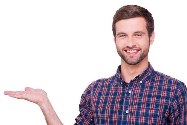 Skopiuj miejsce w ręku. portret przystojnego młodzieńca w koszuli na co dzień, trzymającego miejsce na kopię i patrzącego na kamerę z uśmiechem, stojąc na białym tle