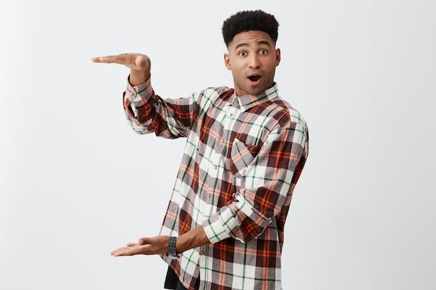 Skopiuj miejsce zabawny ciemnoskóry dojrzały facet ze stylową fryzurą w modnej koszuli gestykuluje rękami, pokazując, że trzyma coś dużego ze zdziwionym wyrazem twarzy.