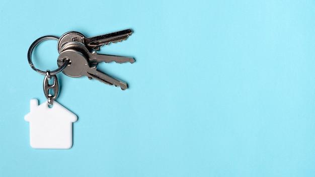 Skopiuj niebieskie tło z kluczami domu