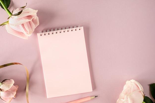 Skopiuj notatnik miejsca na tekst na jasnoróżowym tle z różowymi różami. układanie płaskie, widok z góry